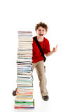 Kid and pile of books. Young boy standing next to pile of books on white background Stock Photos