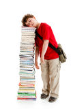 Kid and pile of books. Young boy standing next to pile of books on white background Stock Photo