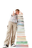 Kid and pile of books. Young boy standing next to pile of books showing Ok sign on white background Royalty Free Stock Images