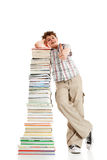 Kid and pile of books - Ok sign. Young boy showing thumb up sign, standing next to pile of books on white background Royalty Free Stock Photo