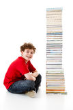 Kid and pile of books. Young boy sitting next to pile of books on white background Stock Photos