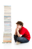 Kid and pile of books. Young boy sitting next to pile of books on white background Stock Photo