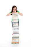 Kid and pile of books. Young girl standing next to pile of books on white background Royalty Free Stock Photos