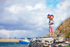 Kid with pinwheel standing on the cliff near seaside Stock Photography