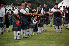 Kid Piper. A young child stands among all of the adult pipers during the closing ceremonies of The 33rd annual Cambridge Highland Games Stock Images
