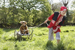 Kid In Pirate Costume Pulling Boy In Jaguar Costume On Cart Royalty Free Stock Photos