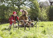 Kid In Pirate Costume Pushing Boy In Jaguar Costume On Cart Stock Image