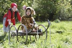 Kid In Pirate Costume Pushing Boy In Jaguar Costume On Cart Royalty Free Stock Image