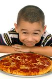 Kid and pizza 5 years old. A 5-year-old hispanic boy ready to eat a pepperoni pizza, isolated on white Royalty Free Stock Image