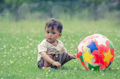 Kid play funny ball on the grass field Stock Photo