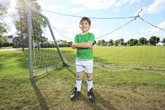 Kid play soccer on a field Stock Images