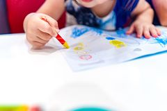 Kid play, study and learn how to color and draw the crayon color in to the paper with her parents stock photos