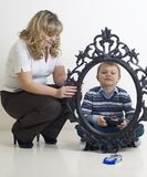 Kid play with toy car. Mom hold a frame stock images