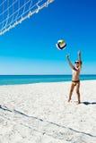 Kid play volleyball on sea beach Stock Photos