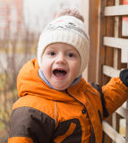The kid at a playground in autumn day is surprised and admires, Royalty Free Stock Image