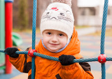 The kid at a playground holds a rope ladder in the fall Royalty Free Stock Photo