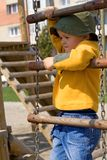 Kid playing. Little boy climbing up a chain ladder on the playground royalty free stock image