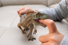 Kid playing an allosaurus toy and putting his finger inside the mouth stock images