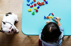 Kid playing with alphabetic toys sitting next to pet dog