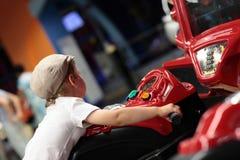 Kid playing arcade simulator machine. At an amusement park Royalty Free Stock Photography