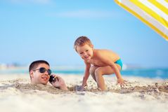 Kid playing around father's head in sand, talking on the cell phone Royalty Free Stock Photos