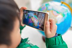 Kid playing Augmented Reality popup globe with famous buildings via mobile. Zhongshan,China-February 7, 2018:kid playing Augmented Reality popup globe with Stock Image