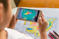 Kid playing Augmented Reality popup paintings of a filled dolphin via mobile Royalty Free Stock Images