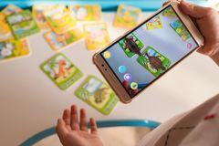 Kid playing Augmented Reality popup of tyrannosaurus and ankylosaurus via mobile stock photography
