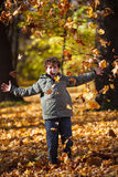 Kid playing in autumn park Royalty Free Stock Images