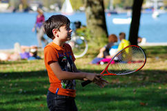 Kid playing badminton. Boy playing badminton on a medow near the beach of a lake Royalty Free Stock Photo