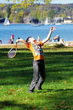 Kid playing badminton. Boy playing badminton on a medow near the beach of a lake Stock Photography