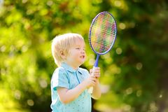 Kid playing badminton in summer park Stock Images