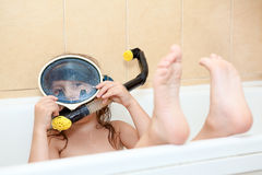 Kid playing in bath with snorkel and mask Stock Image