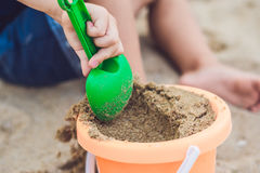 Kid playing on the beach with the children`s shovel and a bucket Royalty Free Stock Images