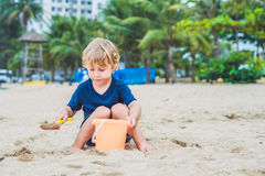 Kid playing on the beach with the children`s shovel and a bucket Royalty Free Stock Photos