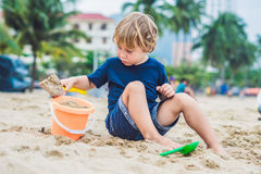 Kid playing on the beach with the children`s shovel and a bucket stock photo