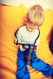 Kid playing with big professional digital camera Stock Images
