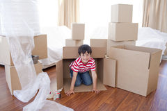 Kid playing with boxes in new house Stock Images