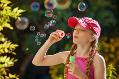 Kid playing with bubble pipe royalty free stock photography