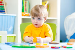 Kid playing with building blocks at home or kindergarten Stock Photos