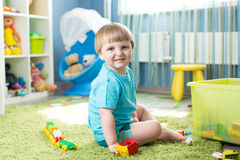 Kid playing with building blocks at home or kindergarten royalty free stock photography