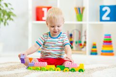 Kid playing with building blocks at kindergarten Stock Images