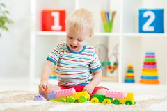 Kid playing with building blocks at kindergarten Stock Image