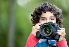 Kid playing with a camera Royalty Free Stock Photos