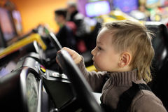 Kid playing with car simulator Stock Image
