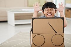 Kid playing with cardboard car. Happy little Vietnamese boy in carboard automobile Royalty Free Stock Images