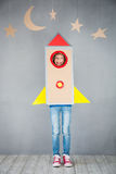 Kid playing with cardboard rocket at home Stock Images