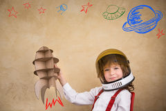 Kid playing with cardboard toy rocket. Kid astronaut with cardboard toy rocket. Child playing at home. Earth day concept Stock Images