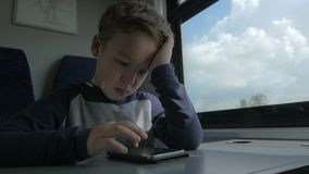 Kid playing on cell when traveling by train. Slow motion shot of a boy traveling by express train. Bored child trying to fill the time with mobile game. Scene stock video footage