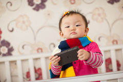 Kid playing cellphone. In bed Stock Photography